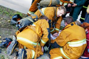 rescue operation. Team of fireman making artificial respiration to the fire victim. Authentic shot. may be little blurred
